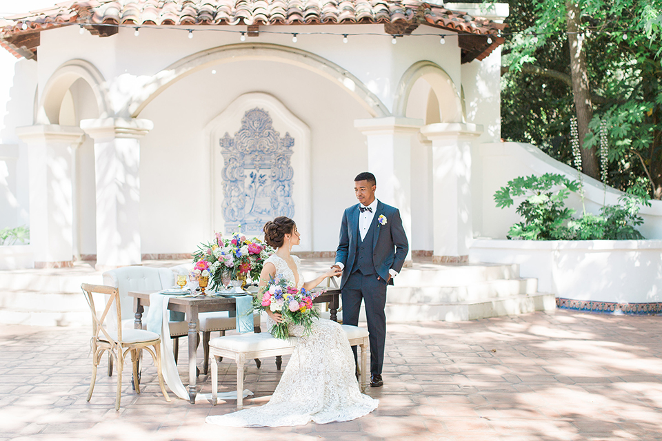 Rancho las lomas outdoor wedding shoot with spanish inspiration bride form fitting lace gown with beaded detail and a plunging neckline with open back design with groom slate blue notch lapel suit with a matching vest and white dress shirt with a matching slate pipe edge bow tie bride sitting at table with pink and blue colorful floral bridal bouquet