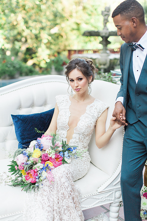 Rancho las lomas outdoor wedding shoot with spanish inspiration bride form fitting lace gown with beaded detail and a plunging neckline with open back design with groom slate blue notch lapel suit with a matching vest and white dress shirt with a matching slate pipe edge bow tie bride sitting on white couch holding hands and holding pink and blue colorful floral bridal bouquet