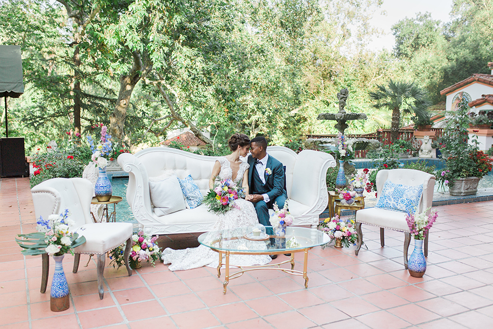 Rancho las lomas outdoor wedding shoot with spanish inspiration bride form fitting lace gown with beaded detail and a plunging neckline with open back design with groom slate blue notch lapel suit with a matching vest and white dress shirt with a matching slate pipe edge bow tie sitting on white couch with bride holding pink and blue floral bridal bouquet
