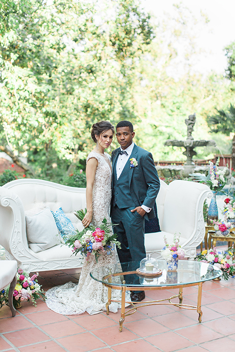 Rancho las lomas outdoor wedding shoot with spanish inspiration bride form fitting lace gown with beaded detail and a plunging neckline with open back design with groom slate blue notch lapel suit with a matching vest and white dress shirt with a matching slate pipe edge bow tie standing by couch and bride holding pink and blue colorful bridal floral bouquet