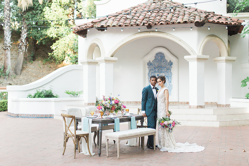 Rancho las lomas outdoor wedding shoot with spanish inspiration bride form fitting lace gown with beaded detail and a plunging neckline with open back design with groom slate blue notch lapel suit with a matching vest and white dress shirt with a matching slate pipe edge bow tie standing by table bride holding pink and blue colorful floral bridal bouquet