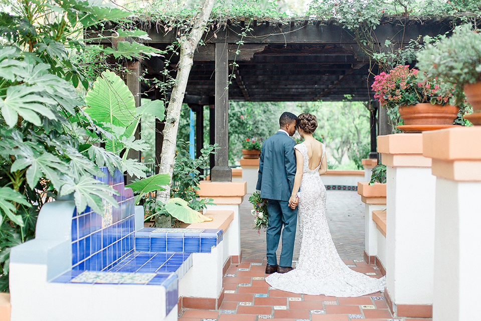 Rancho las lomas outdoor wedding shoot with spanish inspiration bride form fitting lace gown with beaded detail and a plunging neckline with open back design with groom slate blue notch lapel suit with a matching vest and white dress shirt with a matching slate pipe edge bow tie holding hands and groom holding pink and blue colorful floral bridal bouquet