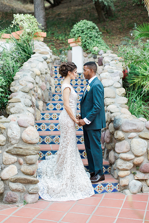 Rancho las lomas outdoor wedding shoot with spanish inspiration bride form fitting lace gown with beaded detail and a plunging neckline with open back design with groom slate blue notch lapel suit with a matching vest and white dress shirt with a matching slate pipe edge bow tie holding hands and stairs