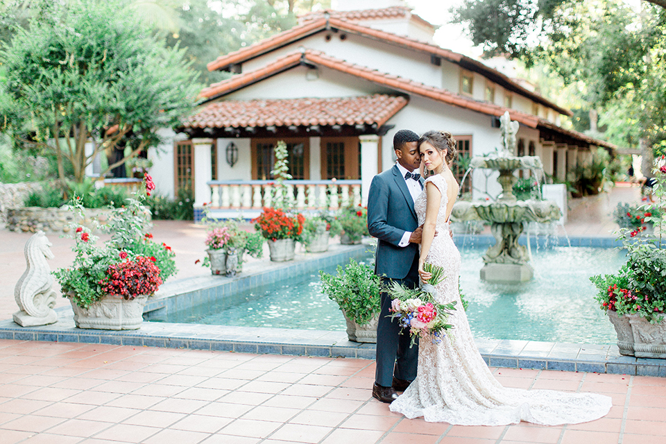 Rancho las lomas outdoor wedding shoot with spanish inspiration bride form fitting lace gown with beaded detail and a plunging neckline with open back design with groom slate blue notch lapel suit with a matching vest and white dress shirt with a matching slate pipe edge bow tie hugging and bride holding pink and blue colorful floral bridal bouquet