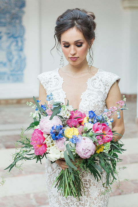 Rancho las lomas outdoor wedding shoot with spanish inspiration bride form fitting lace gown with beaded detail and a plunging neckline with open back design holding pink and blue colorful floral bridal bouquet close up