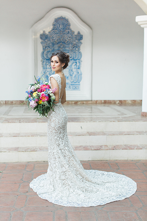 Rancho las lomas outdoor wedding shoot with spanish inspiration bride form fitting lace gown with beaded detail and a plunging neckline with open back design holding pink and blue colorful floral bridal bouquet