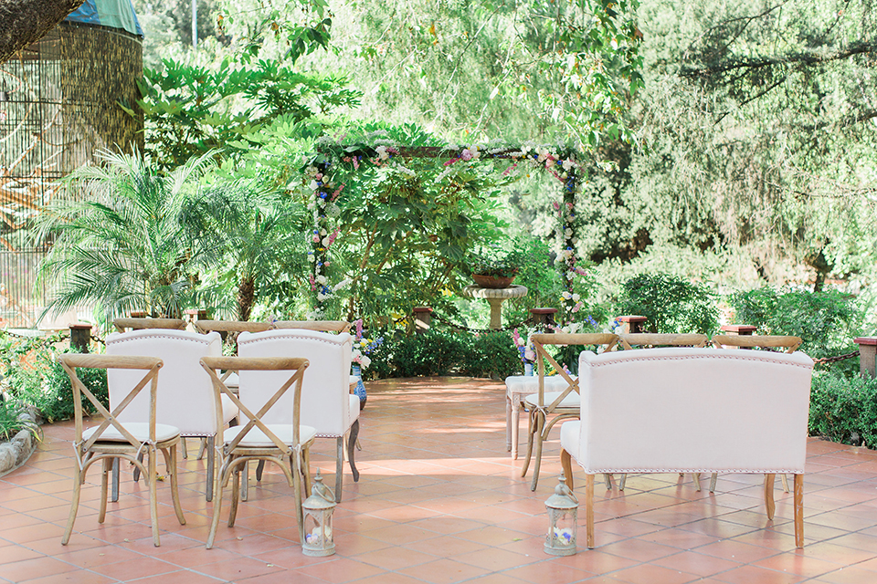 Rancho las lomas outdoor wedding with spanish inspiration wedding ceremony set up with lush greenery backdrop and wood altar with flower decor and white vintage chairs for ceremony wedding photo idea