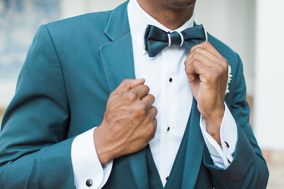 Rancho las lomas outdoor wedding with spanish inspiration groom slate blue notch lapel suit with a matching vest and white dress shirt with a matching slate blue pipe edge bow tie and white floral boutonniere close up