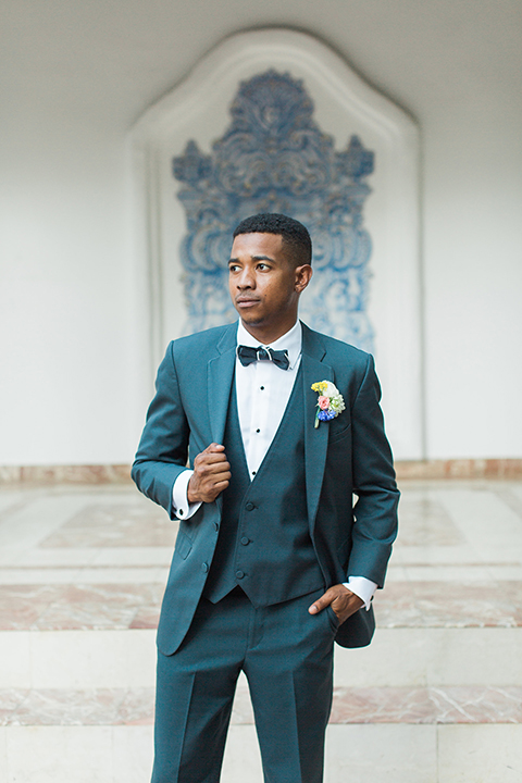 Rancho las lomas outdoor wedding with spanish inspiration groom slate blue notch lapel suit with a matching vest and white dress shirt with a matching slate blue pipe edge bow tie and white floral boutonniere holding jacket