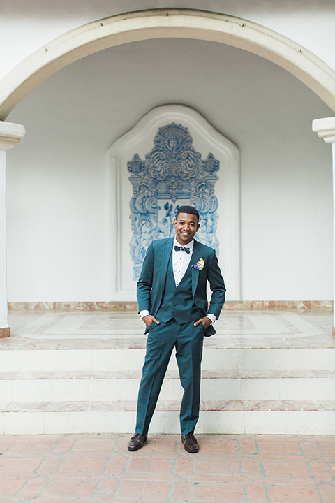 Rancho las lomas outdoor wedding with spanish inspiration groom slate blue notch lapel suit with a matching vest and white dress shirt with a matching slate blue pipe edge bow tie and white floral boutonniere