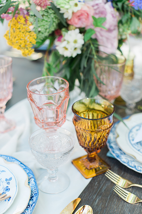 Rancho las lomas outdoor wedding with spanish inspiration table set up light grey wood table with white vintage chairs and light blue napkin decor with white and blue place settings with pink and blue colorful flower centerpiece decor and yellow glasses with gold silverware
