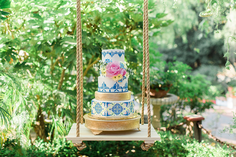 Rancho las lomas outdoor wedding with spanish inspiration table set up light grey wood table with white vintage chairs and light blue napkin decor with white and blue place settings with pink and blue colorful flower centerpiece decor and yellow glasses with gold silverware with wedding cake three tier white and blue patterned cake with gold accents and pink flowers hanging on wood table