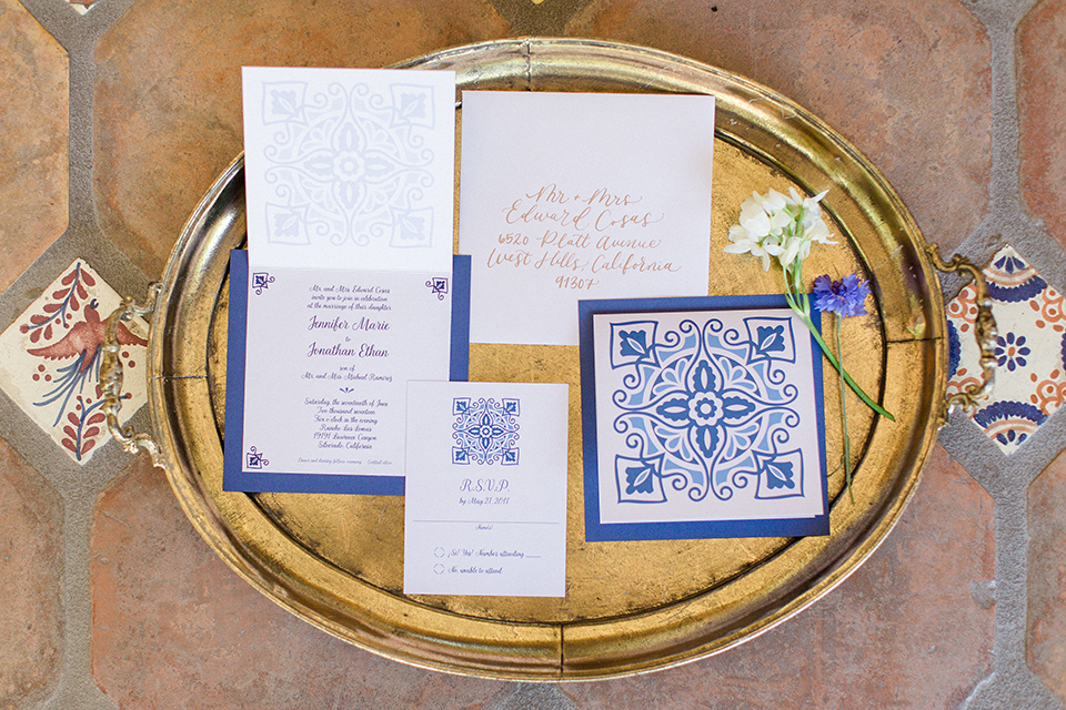 Rancho las lomas outdoor wedding with spanish inspiration wedding invitations white and blue patterned wedding invitations with blue writing and white and blue flower decor on gold tray for background wedding photo idea for wedding invitations