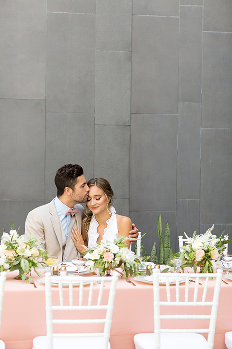 San diego wedding at the hilton bayside bride short white dress with a lace halter bodice and chiffon skirt with groom tan notch lapel suit with a light blue dress shirt and a blush pink bow tie sitting at table kissing