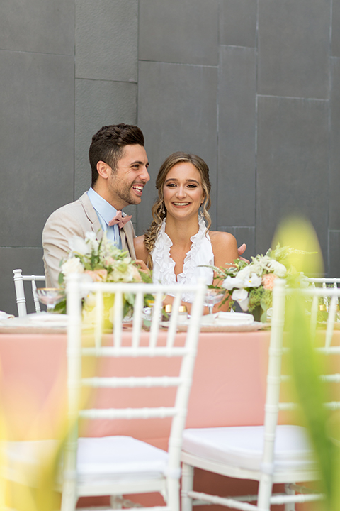 San diego wedding at the hilton bayside bride short white dress with a lace halter bodice and chiffon skirt with groom tan notch lapel suit with a light blue dress shirt and a blush pink bow tie sitting at table smiling