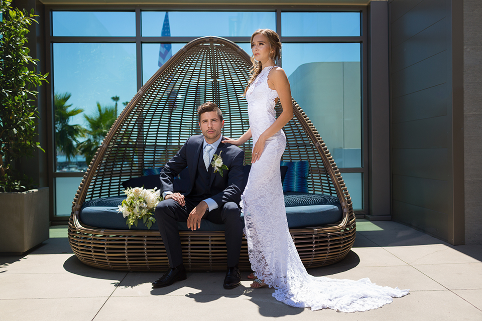 San diego wedding at the hilton bayside bride form fitting lace gown with a high halter neckline and slit in leg area with groom navy notch lapel suit with a light blue dress shirt and a light blue striped long tie with a white and green floral boutonniere sitting on couch with green and white floral bridal bouquet with bride standing