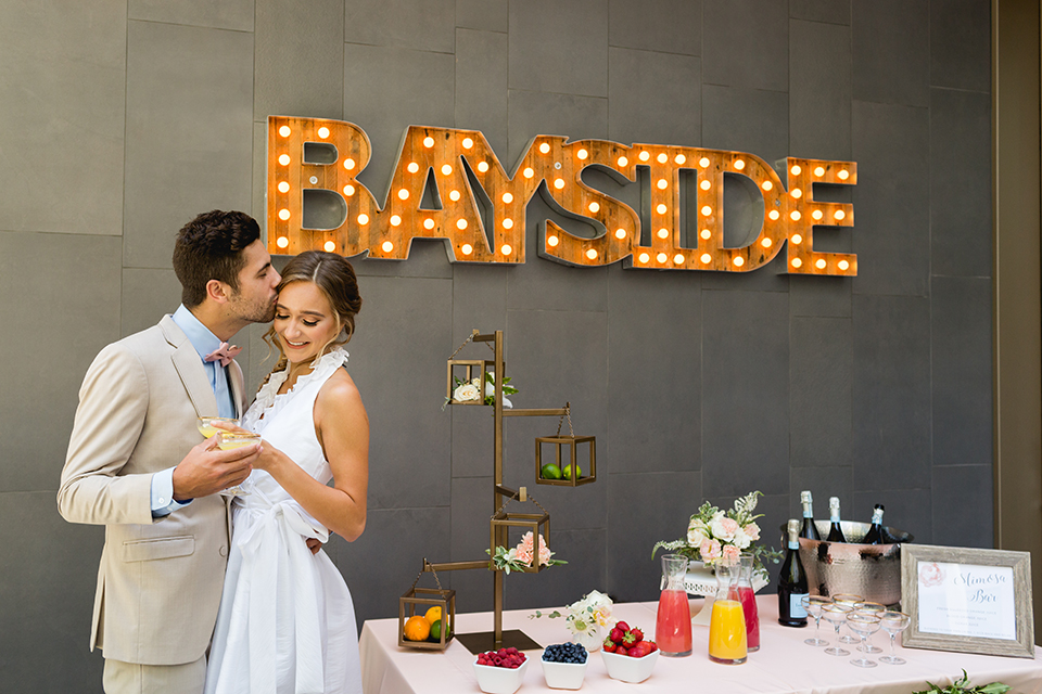 San diego wedding at the hilton bayside bride short white dress with a lace halter bodice and chiffon skirt with groom tan notch lapel suit with a light blue dress shirt and a blush pink bow tie standing by drinks table hugging and holding drinks with sign in background