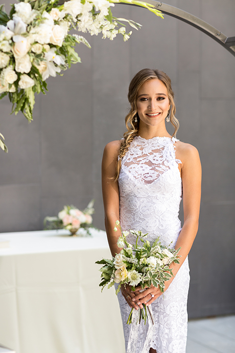 San diego wedding at the hilton bayside bride form fitting lace gown with a high halter neckline and slit in leg area standing and holding white and green floral bridal bouquet close up