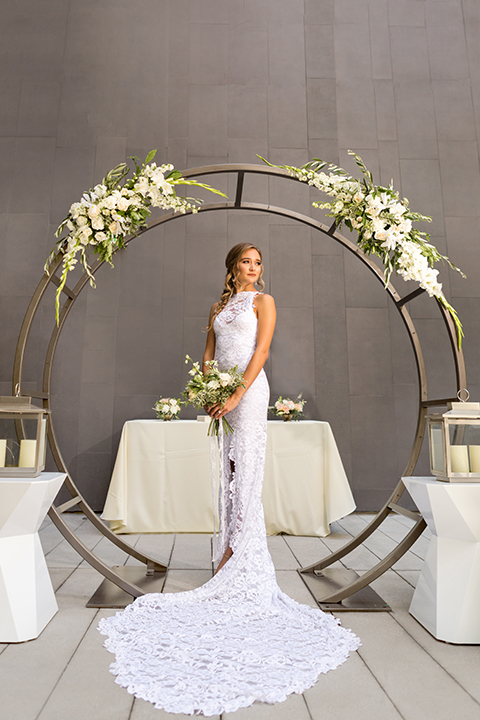San diego wedding at the hilton bayside bride form fitting lace gown with a high halter neckline and slit in leg area standing and holding white and green floral bridal bouquet