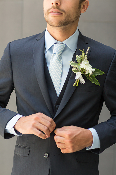 San diego wedding at the hilton bayside groom navy notch lapel suit with a matching vest and light blue dress shirt with a matching light blue long striped tie with a white and green floral boutonniere close up
