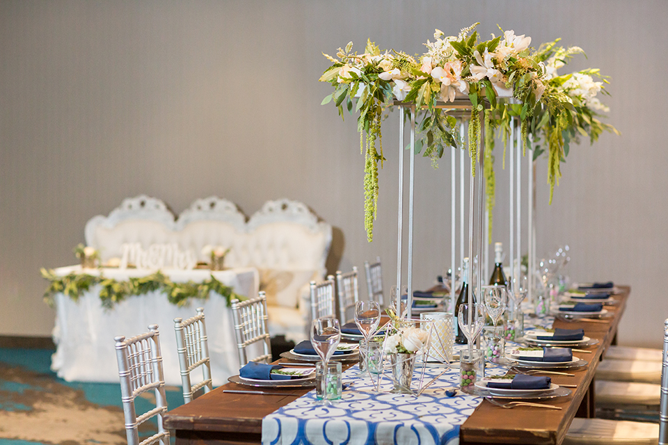 San diego wedding at the hilton bayside table set up brown wood table with white and clear place settings with blue linen napkin decor and white and blue table runner with white and green tall flower centerpiece decor in clear vases with white chiavari chairs