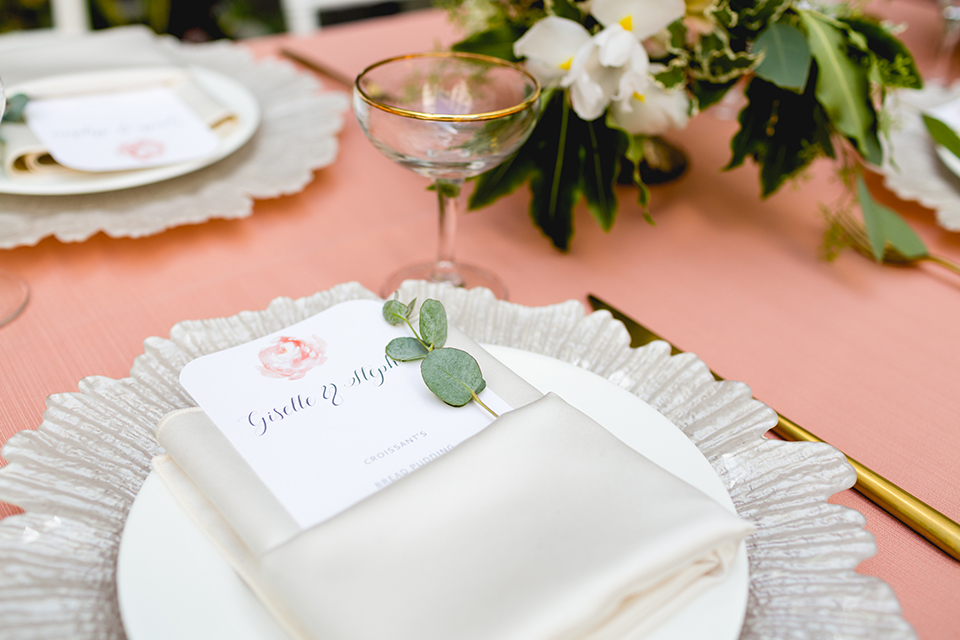 San diego wedding at the hilton bayside table set up with blush pink table linen and white chiavari chairs with white place settings and silver linen napkin decor with short white and green flower centerpiece decor with glassware and silverware