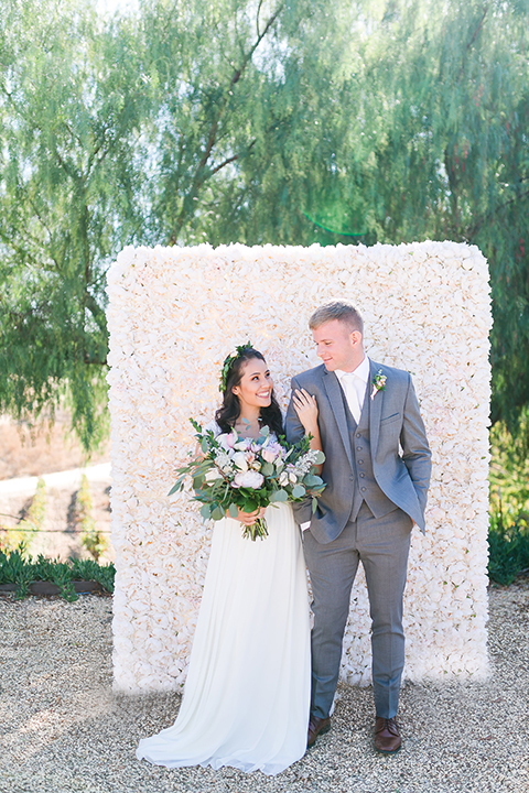 Temecula outdoor wedding at bel vino winery bride a line chiffon gown with straps and lace detail on bodice with a sweetheart neckline and white and green flower crown with groom grey notch lapel suit with a matching vest and white dress shirt with a long white tie and white and pink floral boutonniere holding hands