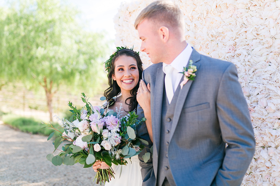 Temecula outdoor wedding at bel vino winery bride a line chiffon gown with straps and lace detail on bodice with a sweetheart neckline and white and green flower crown with groom grey notch lapel suit with a matching vest and white dress shirt with a long white tie and white and pink floral boutonniere hugging and holding hands bride holding white and green floral bridal bouquet