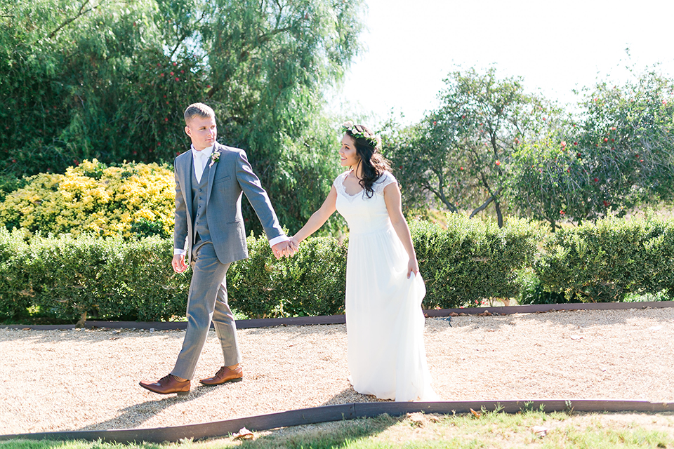 Temecula outdoor wedding at bel vino winery bride a line chiffon gown with straps and lace detail on bodice with a sweetheart neckline and white and green flower crown with groom grey notch lapel suit with a matching vest and white dress shirt with a long white tie and white and pink floral boutonniere holding hands and walking