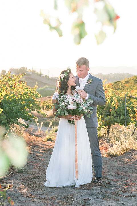 Temecula outdoor wedding at bel vino winery bride a line chiffon gown with straps and lace detail on bodice with a sweetheart neckline and white and green flower crown with groom grey notch lapel suit with a matching vest and white dress shirt with a long white tie and white and pink floral boutonniere hugging and smiling bride holding white and green floral bridal bouquet