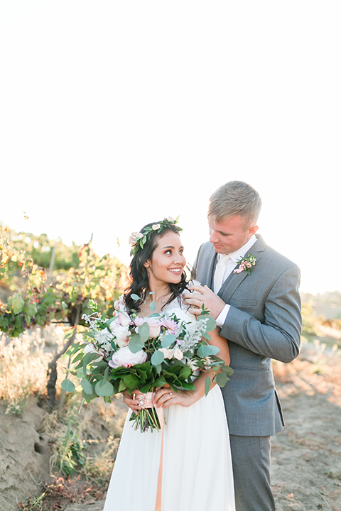 Temecula outdoor wedding at bel vino winery bride a line chiffon gown with straps and lace detail on bodice with a sweetheart neckline and white and green flower crown with groom grey notch lapel suit with a matching vest and white dress shirt with a long white tie and white and pink floral boutonniere hugging and bride holding white and green floral bridal bouquet