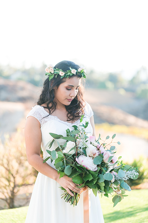 Temecula outdoor wedding at bel vino winery bride a line chiffon gown with straps and lace detail on bodice with a sweetheart neckline and white and green flower crown holding white and green floral bridal bouquet