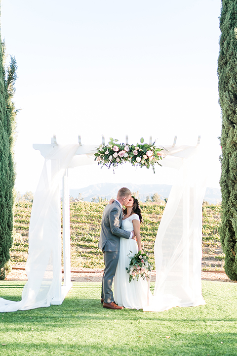 Temecula outdoor wedding at bel vino winery bride a line chiffon gown with straps and lace detail on bodice with a sweetheart neckline and white and green flower crown with groom grey notch lapel suit with a matching vest and white dress shirt with a long white tie and white and pink floral boutonniere kissing during ceremony and bride holding white and green floral bridal bouquet