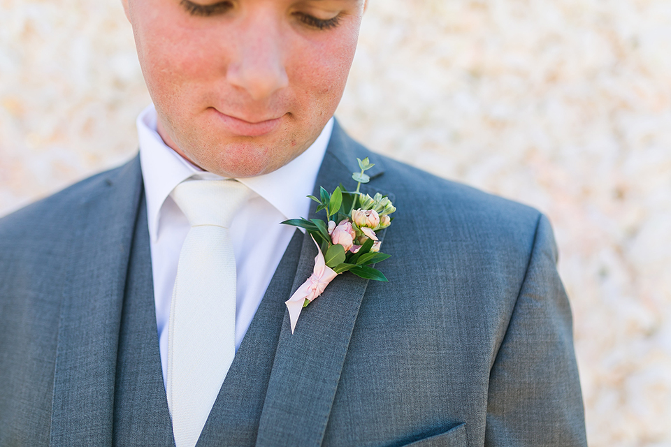 Temecula outdoor wedding at bel vino winery groom grey notch lapel suit with a matching vest and white dress shirt with a long white tie and white and pink floral boutonniere close up