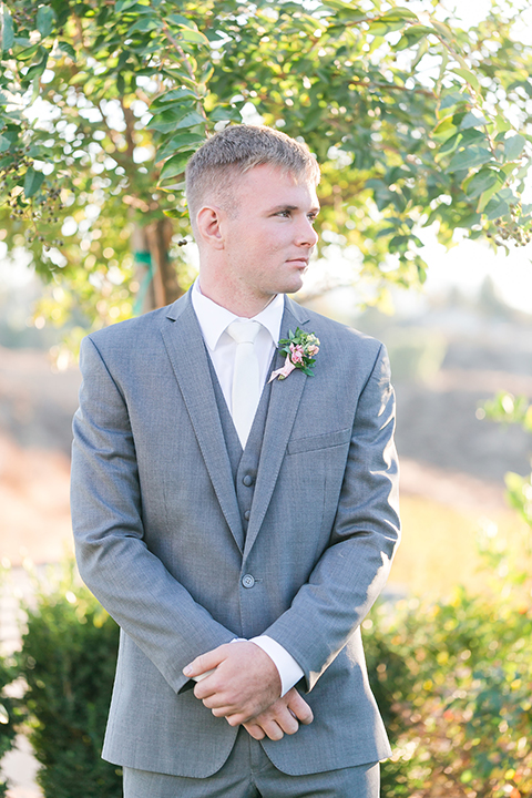 Temecula outdoor wedding at bel vino winery groom grey notch lapel suit with a matching vest and white dress shirt with a long white tie and white and pink floral boutonniere standing and crossing hands