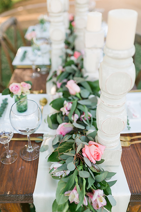 Temecula outdoor wedding at bel vino winery table set up dark brown wood table with white square place settings and pink and green garland flower decor in center and gold silverware decor with matching brown chairs and white table runner