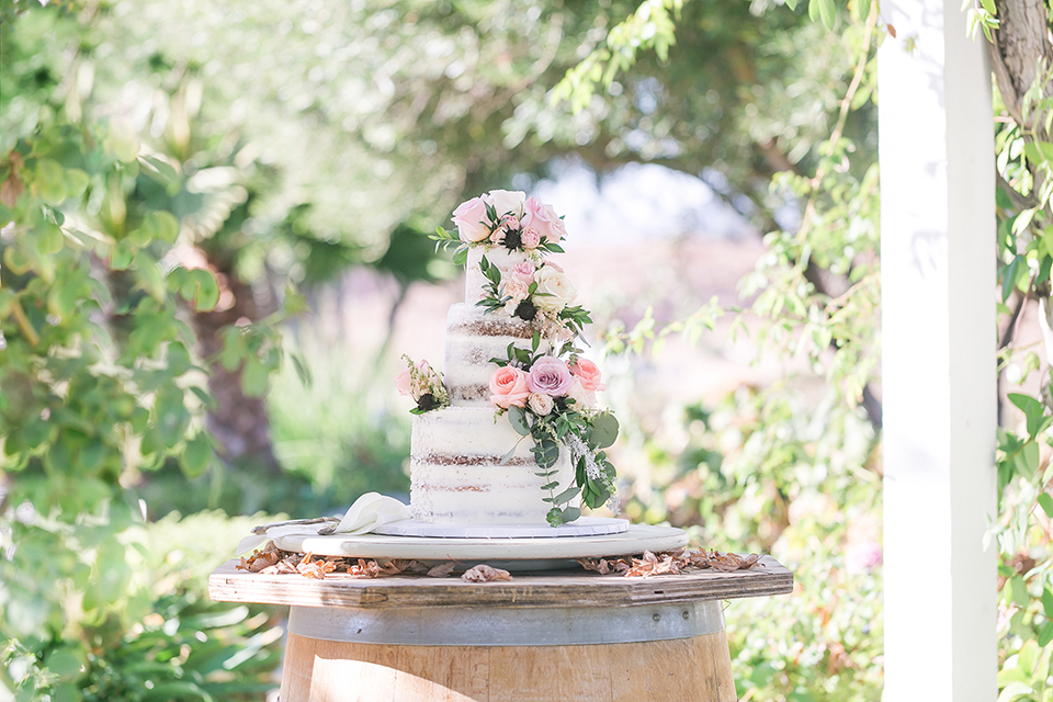 Temecula outdoor wedding at bel vino winery wedding cake three tier white bare wedding cake with pink and green flower decor on side with white tray on wine barrel wedding photo idea for wedding cake