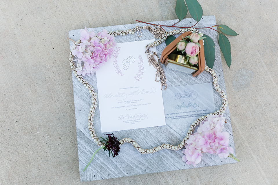 Temecula outdoor wedding at bel vino winery white wedding invitations with grey marble background with pink flowers on edge and greenery decor with jewelry decor wedding photo idea for invitations
