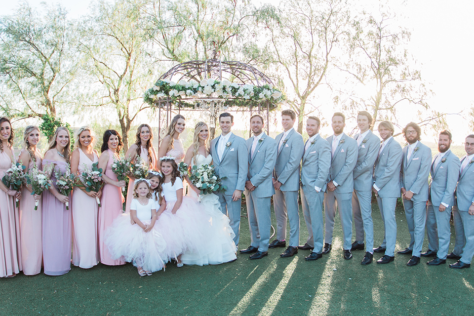 Temecula outdoor wedding at falkner winery bride mermaid style gown with lace bodice and sweetheart neckline with ruffled skirt and long veil with groom heather grey suit with white dress shirt and long white tie with matching pocket square and white floral boutonniere with bridesmaids long blush pink dresses holding white and green floral bridal bouquets and groomsmen heather grey suits with long white ties