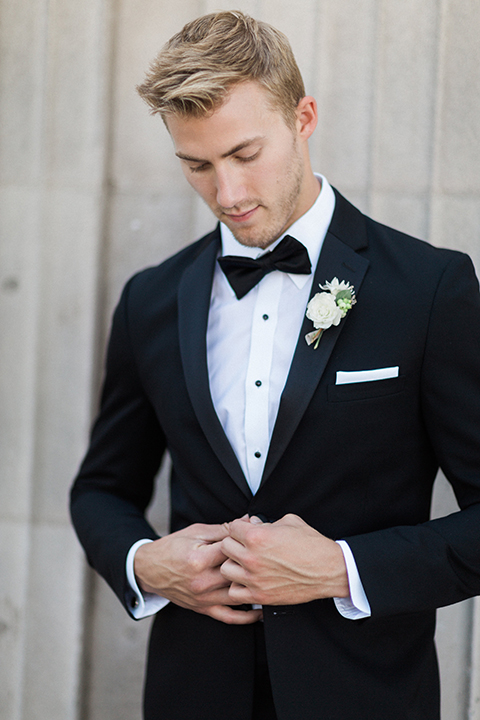 Boutonniere style black notch lapel tuxedo with a black bow tie and a simple white floral boutonniere front view