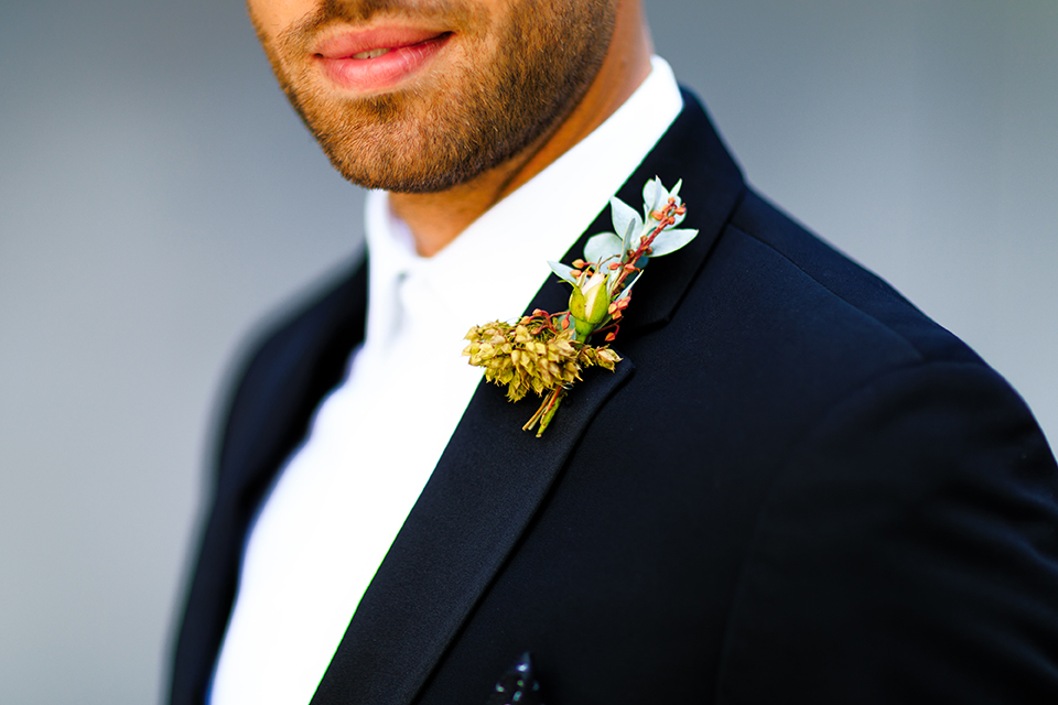 Boutonniere style black notch lapel tuxedo with a white long tie and greenery floral boutonniere