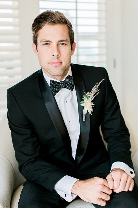 Boutonniere-style-black-shawl-lapel-tuxedo-with-a-black-and-white-dot-bow-tie-and-large-floral-boutonniere