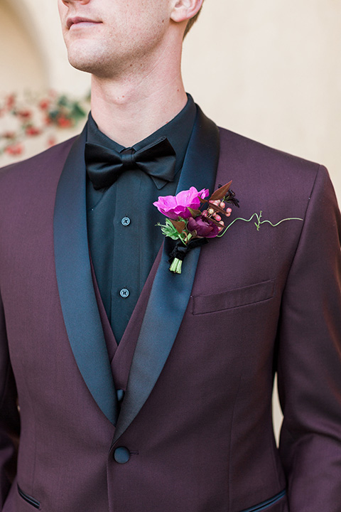 Boutonniere-style-burgundy-shawl-lapel-tuxedo-with-a-black-shirt-and-black-bow-tie-with-a-pink-floral-boutonniere