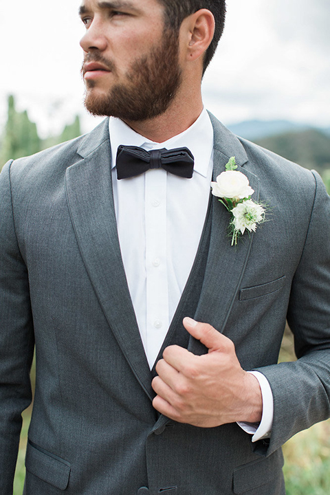 Boutonniere-style-charcoal-grey-notch-lapel-suit-with-a-black-bow-tie-and-white-floral-boutonniere