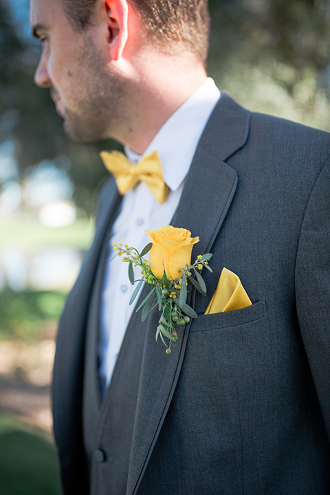 Boutonniere-style-charcoal-grey-notch-lapel-suit-with-a-yellow-bow-tie-and-matching-yellow-floral-boutonniere