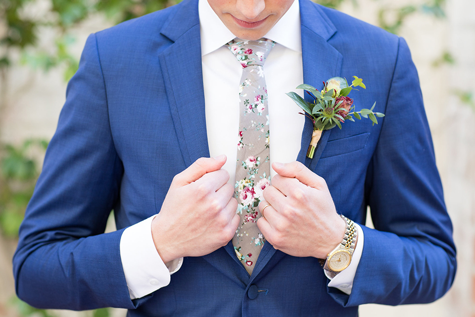 Boutonniere-style-cobalt-blue-notch-lapel-suit-with-a-grey-floral-long-tie-and-a-greenery-floral-boutonniere