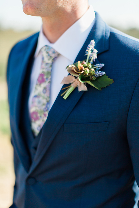 Boutonniere-style-cobalt-blue-notch-lapel-suit-with-a-white-floral-tie-and-greenery-and-blue-floral-boutonniere