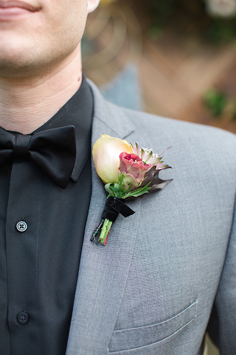 Boutonniere-style-grey-notch-lapel-suit-with-a-black-shirt-and-black-bow-tie-with-a-white-and-pink-floral-boutonniere