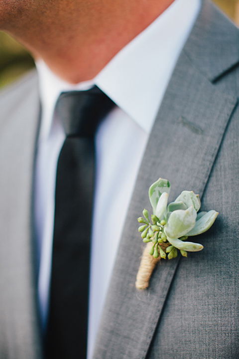 Boutonniere-style-grey-notch-lapel-suit-with-a-long-black-tie-and-green-succulent-boutonniere