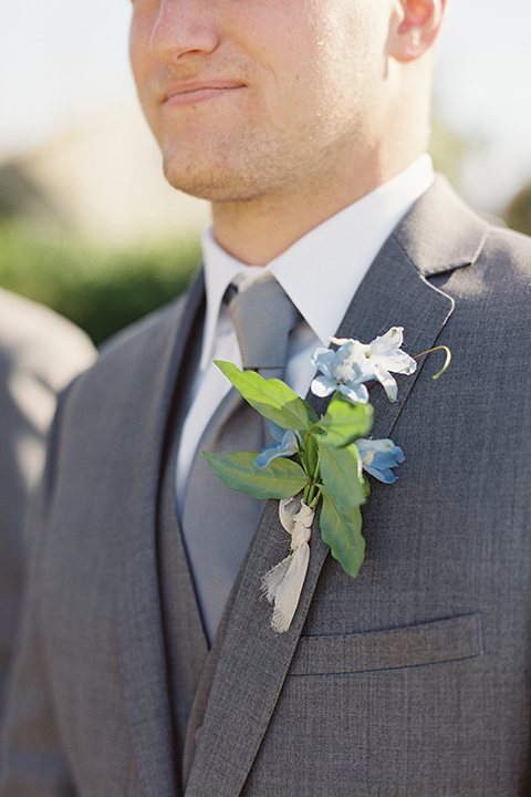 Boutonniere-style-grey-notch-lapel-suit-with-a-matching-grey-long-tie-and-light-blue-floral-boutonniere